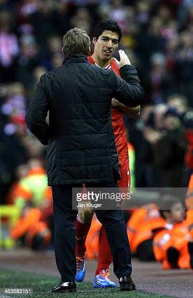 Luis Suarez of Liverpool is congratulated by Manager of Liverpool Brendan Rodgers during the Barclays Premier League match between Liverpool and...