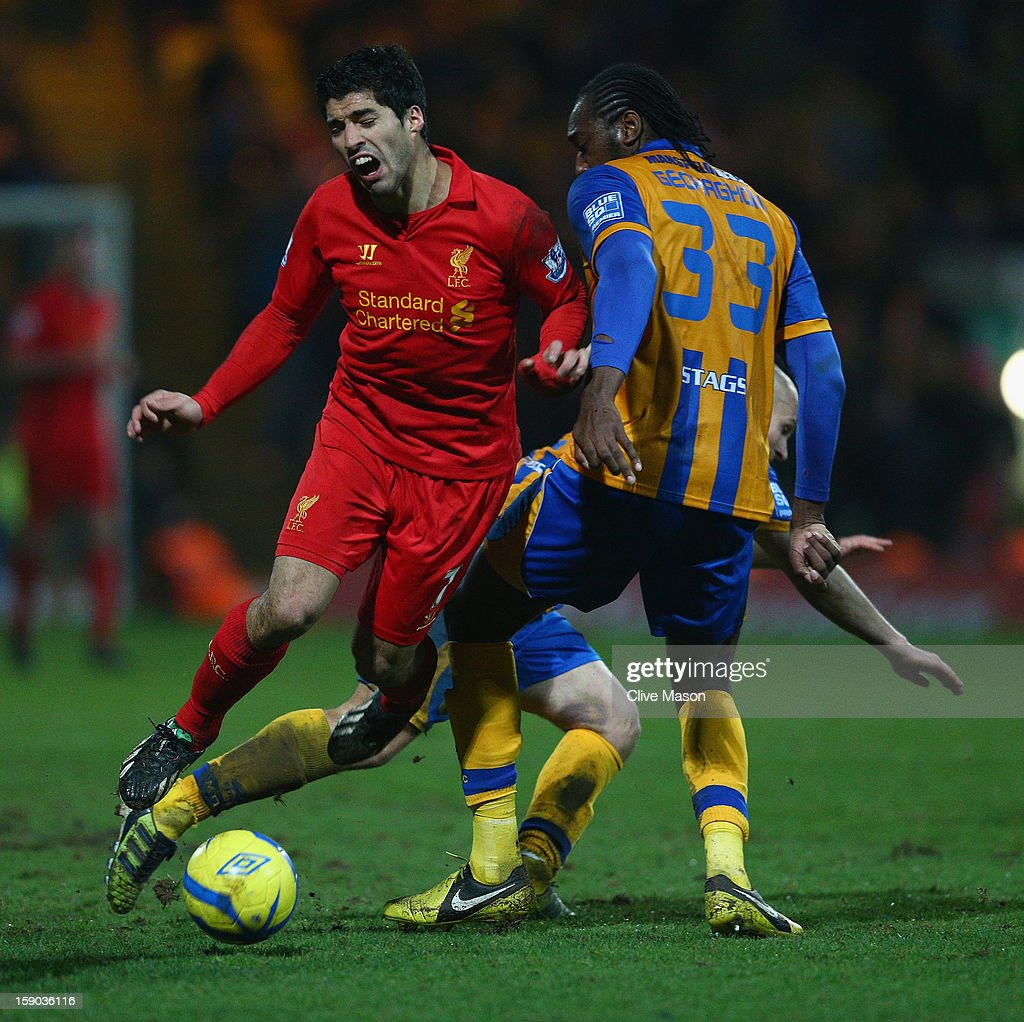 Luis Suarez of Liverpool is tackled by Exodus Geohaghon of Mansfield Town during the FA Cup with Budweiser Third Round match between Mansfield Town and Liverpool at One Call Stadium on January 6, 2013 in Mansfield, England.