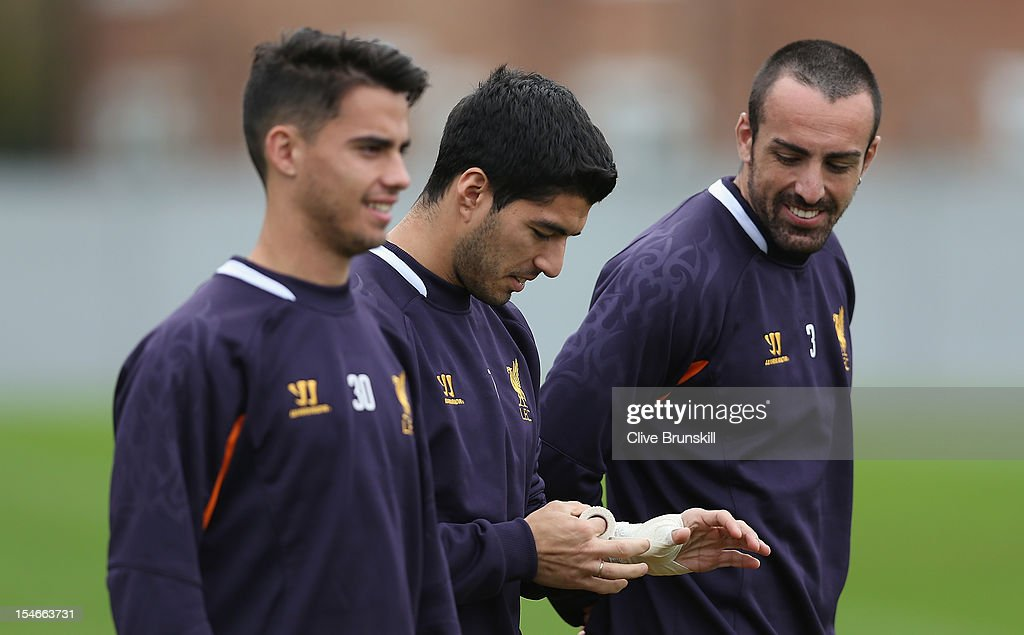 Luis Suarez of Liverpool is watched by Jose Enrique as he wraps his hand with a bandage during a training session ahead of their UEFA Europa League group match against FC Anzhi Makhachkala at Melwood Training Ground on October 24, 2012 in Liverpool, England.