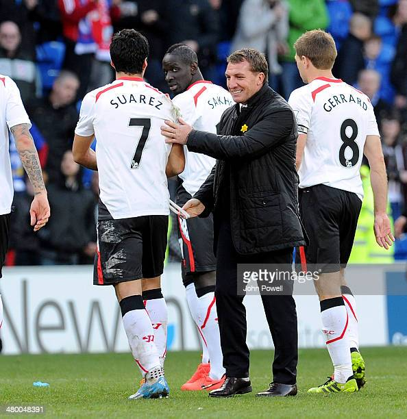 Luis Suarez of Liverpool laughing with manager Brendan Rodgers at the end of the Barclays Premier League match between Cardiff City and Liverpool at...