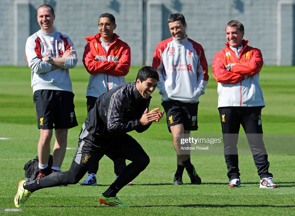 Luis Suarez of Liverpool laughs as <a gi-track='captionPersonalityLinkClicked' href=/galleries/search?phrase=Brendan+Rodgers+-+Voetbalmanager&family=editorial&specificpeople=5446684 ng-click='$event.stopPropagation()'>Brendan Rodgers</a> (R) manager of Liverpool looks on nexte to (L-R) Glen Driscoll, Head of Performance, Zaf Iqbal, First-Team Doctor and Ryland Morgans, Head of Fitness and Conditioning during a training session at Melwood Training Ground on April 18, 2014 in Liverpool, England.