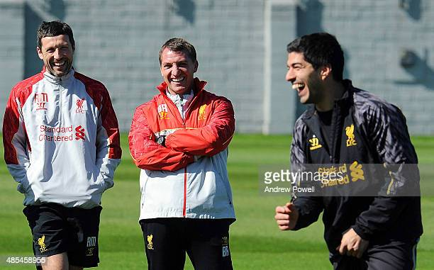 Luis Suarez of Liverpool laughs as Brendan Rodgers manager of Liverpool looks on next to Ryland Morgans Head of Fitness and Conditioning during a...