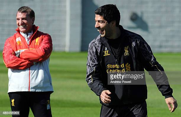 Luis Suarez of Liverpool laughs as Brendan Rodgers manager of Liverpool looks on during a training session at Melwood Training Ground on April 18...