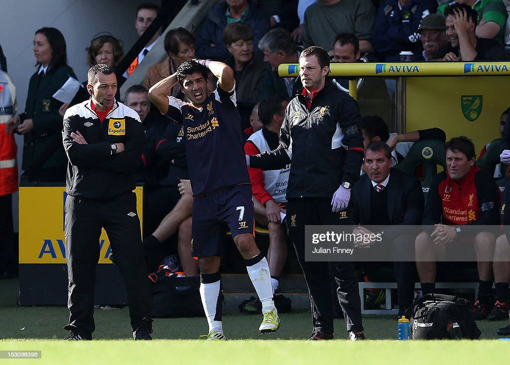 Luis Suarez of Liverpool reacts after a knock to the head during the Barclays Premier League match between Norwich City and Liverpool at Carrow Road on September 29, 2012 in Norwich, England.
