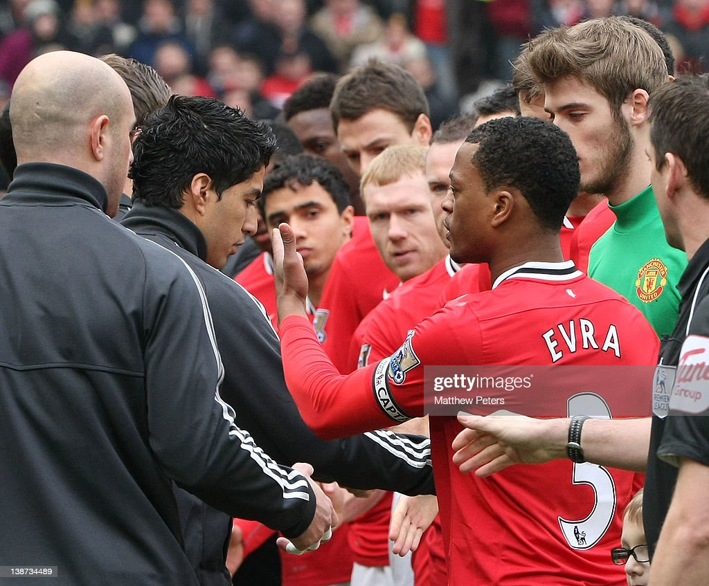 Luis Suarez of Liverpool refuses to shake the hand of <a gi-track='captionPersonalityLinkClicked' href=/galleries/search?phrase=Patrice+Evra&family=editorial&specificpeople=714865 ng-click='$event.stopPropagation()'>Patrice Evra</a> of Manchester United ahead of the Barclays Premier League match between Manchester United and Liverpool at Old Trafford on February 11, 2012 in Manchester, England.