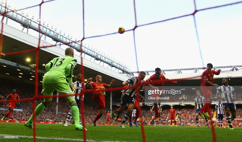 Luis Suarez of Liverpool scores his team's third goal to complete his hat-trick during the Barclays Premier League match between Liverpool and West Bromwich Albion at Anfield on October 26, 2013 in Liverpool, England.