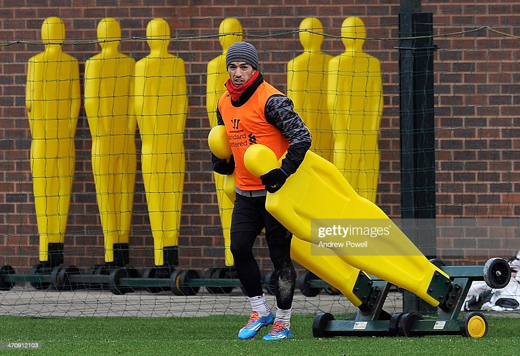 Luis Suarez of Liverpool sets up some training dummies during a training session at Melwood Training Ground on February 21, 2014 in Liverpool, England.