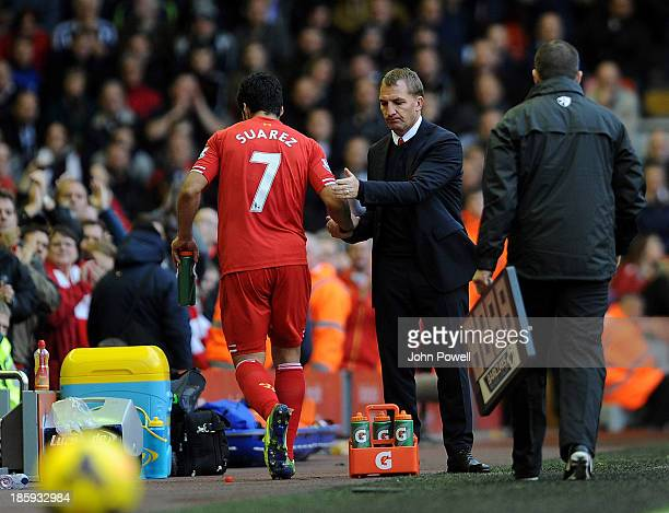 Luis Suarez of Liverpool shakes hands with manager Brendan Rodgers after coming off as substitute during the Barclays Premier League match between...