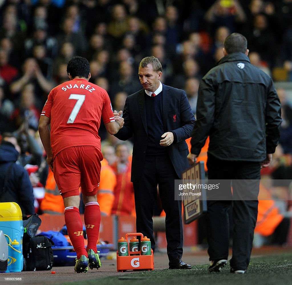 Luis Suarez of Liverpool shakes hands with manager Brendan Rodgers after coming off as substitute during the Barclays Premier League match between Liverpool and West Bromwich Albion at Anfield on October 26, 2013 in Liverpool, England.