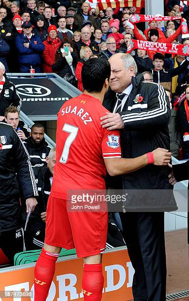 Luis Suarez of Liverpool shankes hands with Fulham manager Martin Jol before the Barclays Premier League Match between Liverpool and Fulham at...