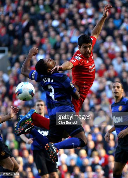 Luis Suarez of Liverpool tangles with Patrice Evra of Manchester United during the Barclays Premier League match between Liverpool and Manchester...