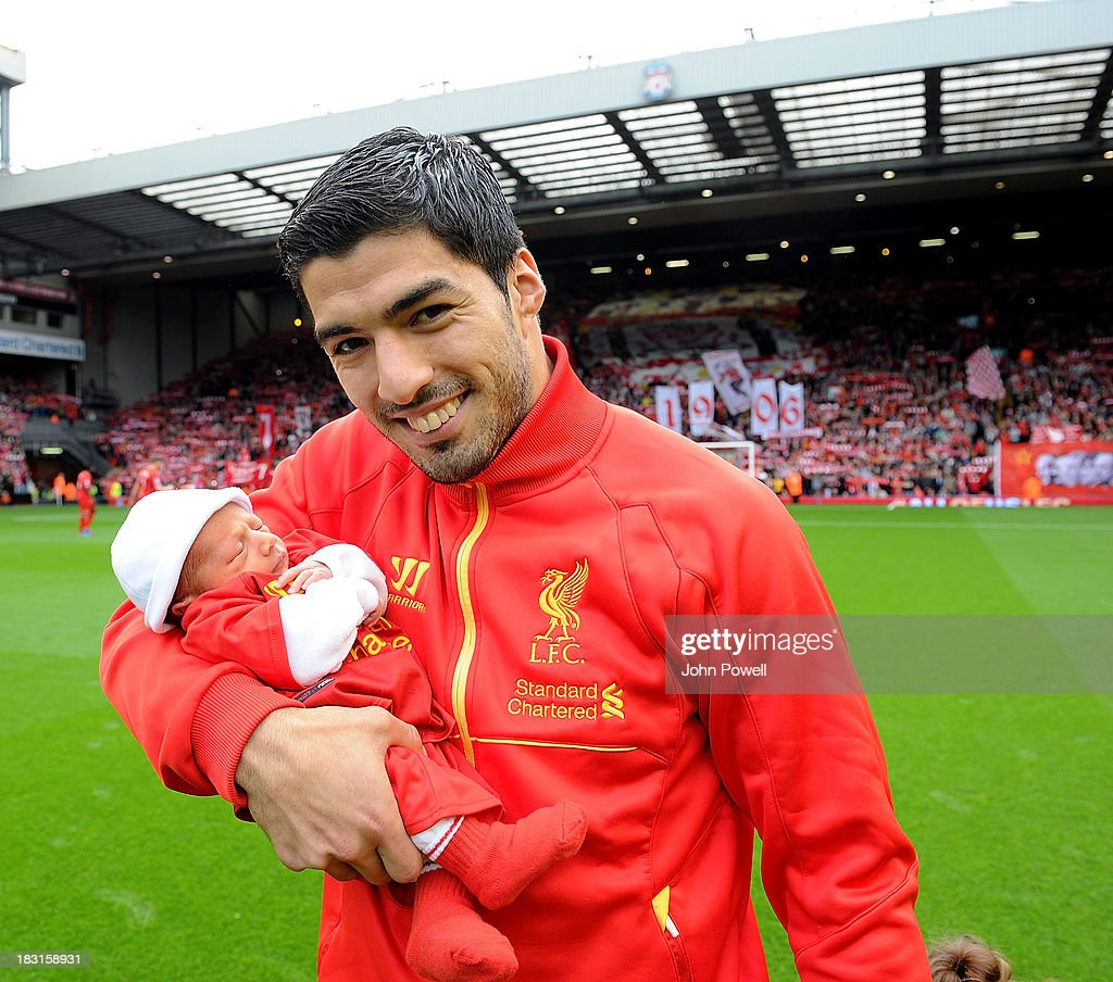 Luis Suarez of Liverpool with his baby son Benja on the pitch before kick off of the Barclays Premier League match between Liverpool and Crystal Palace at Anfield on October 5, 2013 in Liverpool, England.