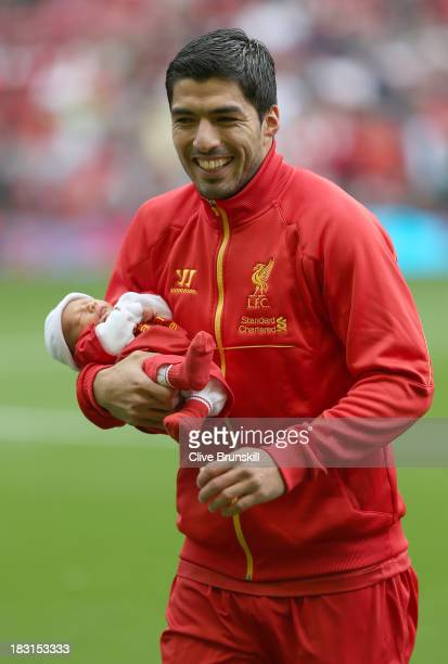 Luis Suarez of Liverpool with his new baby prior to the Barclays Premier League match between Liverpool and Crystal Palace at Anfield on October 5...