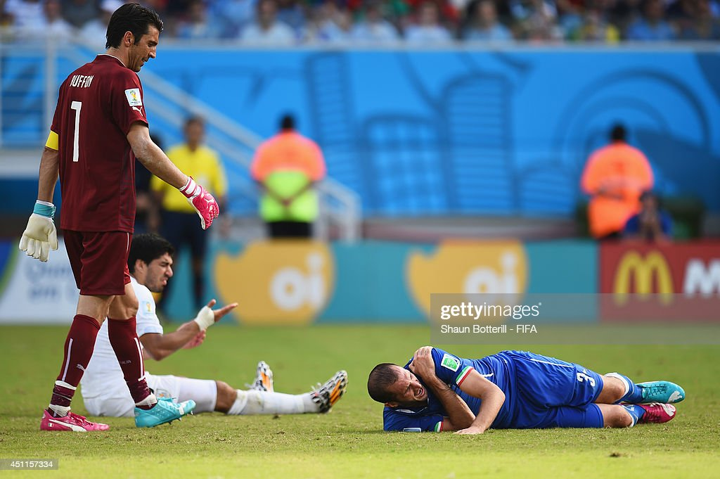 Luis Suarez of Uruguay and <a gi-track='captionPersonalityLinkClicked' href=/galleries/search?phrase=Giorgio+Chiellini&family=editorial&specificpeople=605793 ng-click='$event.stopPropagation()'>Giorgio Chiellini</a> of Italy reacts after a clash during the 2014 FIFA World Cup Brazil Group D match between Italy and Uruguay at Estadio das Dunas on June 24, 2014 in Natal, Brazil.
