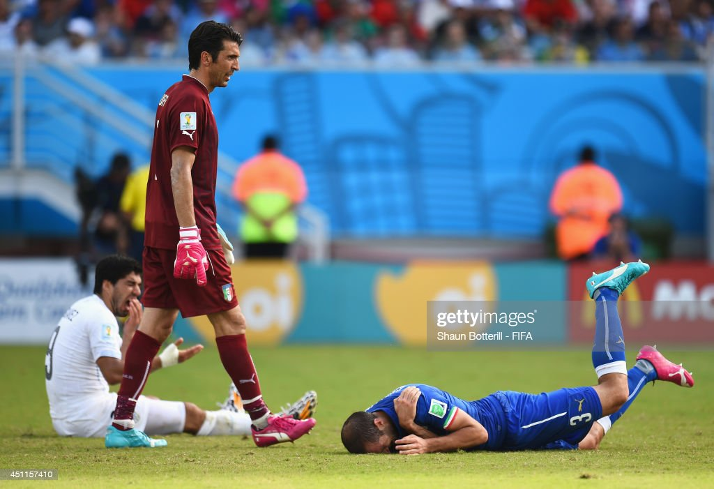 Luis Suarez (L) of Uruguay and <a gi-track='captionPersonalityLinkClicked' href=/galleries/search?phrase=Giorgio+Chiellini&family=editorial&specificpeople=605793 ng-click='$event.stopPropagation()'>Giorgio Chiellini</a> (R) of Italy reacts after a clash during the 2014 FIFA World Cup Brazil Group D match between Italy and Uruguay at Estadio das Dunas on June 24, 2014 in Natal, Brazil.