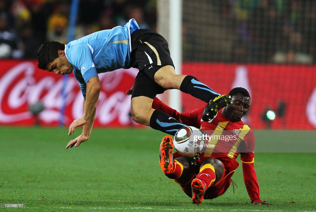 Luis Suarez of Uruguay and <a gi-track='captionPersonalityLinkClicked' href=/galleries/search?phrase=Kwadwo+Asamoah&family=editorial&specificpeople=4376914 ng-click='$event.stopPropagation()'>Kwadwo Asamoah</a> of Ghana challenge for the ball during the 2010 FIFA World Cup South Africa Quarter Final match between Uruguay and Ghana at the Soccer City stadium on July 2, 2010 in Johannesburg, South Africa.