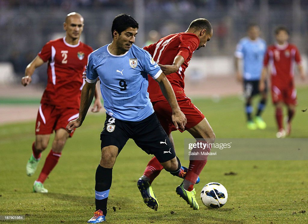 Luis Suarez of Uruguay and Oday Zahran of Jordan compete for the ball during the FIFA 2014 World Cup Qualifier: Intercontinental Play-off First Leg between Jordan and Uruguay on November 13, 2013 in Amman, Jordan.