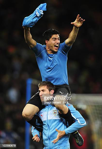 Luis Suarez of Uruguay and team mate celebrate winning the penalty shoot out and progress to the semi finals during the 2010 FIFA World Cup South...
