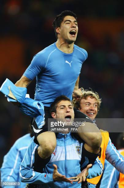 Luis Suarez of Uruguay and team mates celebrate winning the penalty shoot out and progress to the semi finals during the 2010 FIFA World Cup South...