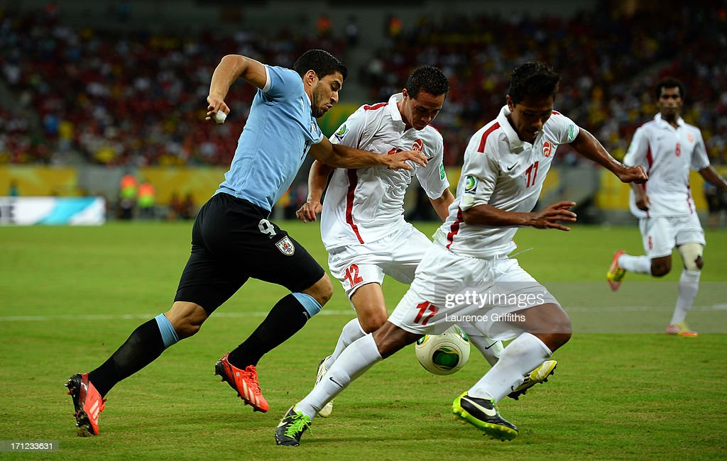 Luis Suarez of Uruguay battles for the ball with Edson Lemaire and Jonathan Tehau of Tahiti during the FIFA Confederations Cup Brazil 2013 Group B match between Uruguay and Tahiti at Arena Pernambuco on June 22, 2013 in Recife, Brazil.