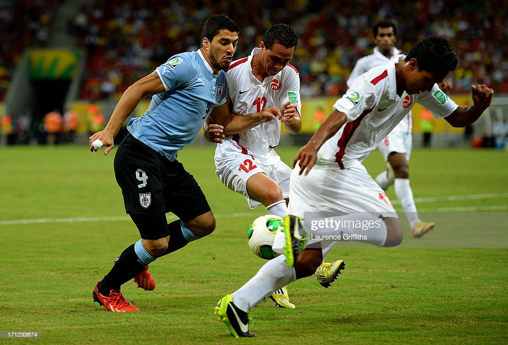 Luis Suarez of Uruguay battles for the ball with Edson Lemaire of Tahiti during the FIFA Confederations Cup Brazil 2013 Group B match between Uruguay and Tahiti at Arena Pernambuco on June 22, 2013 in Recife, Brazil.