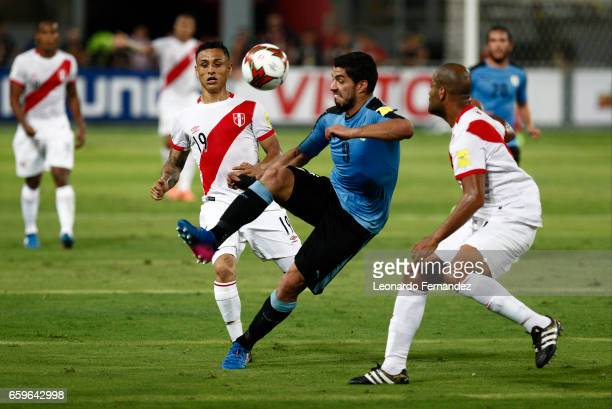 Luis Suarez of Uruguay fights for the ball with Alberto Rodriguez of Peru during a match between Peru and Uruguay as part of FIFA 2018 World Cup at...