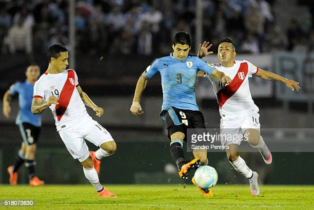 Luis Suarez of Uruguay fights for the ball with Yoshimar Yotun and Christian Cueva of Peru during a match between Uruguay and Peru as part of FIFA...
