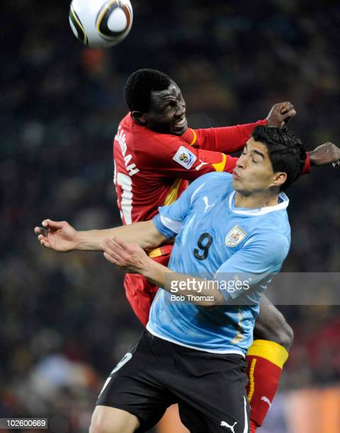Luis Suarez of Uruguay heads the ball with Kwadwo Asamoah of Ghana during the 2010 FIFA World Cup South Africa Quarter Final match between Uruguay...