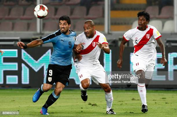Luis Suarez of Uruguay struggles for the ball with Alberto Rodriguez of Peru during a match between Peru and Uruguay as part of FIFA 2018 World Cup...