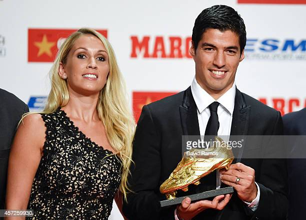 Luis Suarez poses with the Goden Boot Trophy as the best goal scorer in all European Leagues last season with his wife Sofia Balbi on October 15 2014...