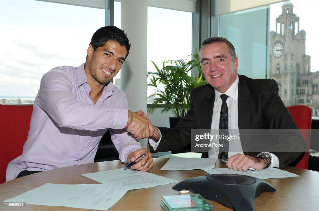 (MINIMUM FEES APPLY - GBP 150 ONLINE OR LOCAL EQUIVALENT, PER IMAGE) Luis Suarez shakes hands with Managing Director of Liverpool FC Ian Ayre after signing a new contract with Liverpool FC at the LFC offices, Chapel St on August 7, 2012 in Liverpool, England.