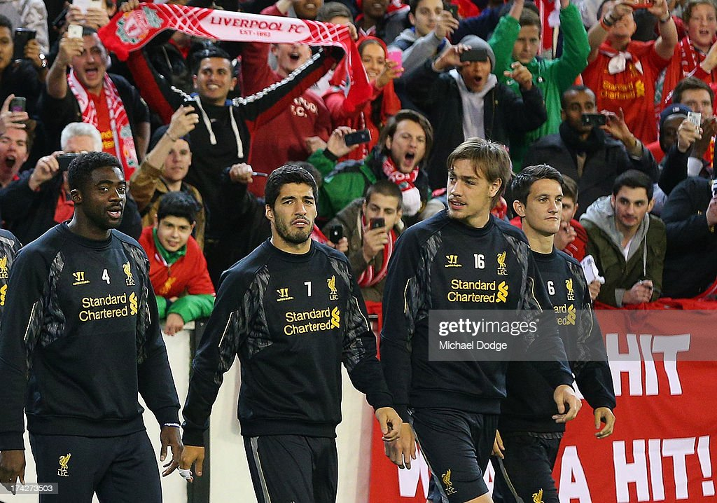 Luis Suarez (C) walks onto the field with teamates in front of the Liverpool fans during a Liverpool FC training session at Melbourne Cricket Ground on July 23, 2013 in Melbourne, Australia.