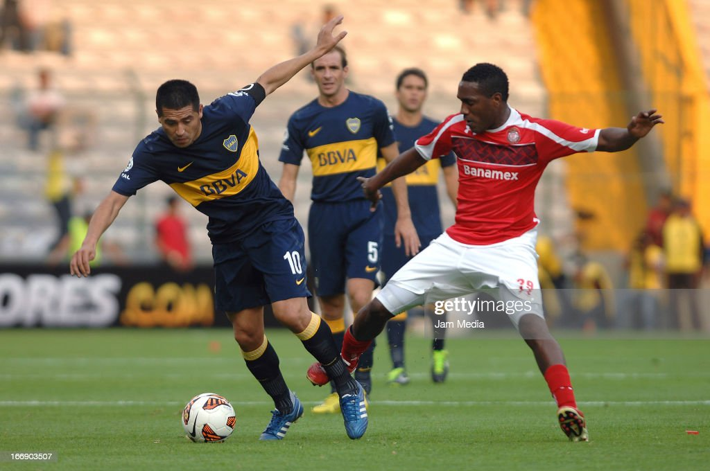 Luis Tejada (R) of Toluca struggles for the ball with <a gi-track='captionPersonalityLinkClicked' href=/galleries/search?phrase=Juan+Roman+Riquelme&family=editorial&specificpeople=243174 ng-click='$event.stopPropagation()'>Juan Roman Riquelme</a> (L) of Boca Juniors during the match between Toluca from Mexico and Boca Jrs from Argentina as part of the Copa Bridgestone Libertadores 2013 at Nemesio Diez Stadium on April 17, 2013 in Toluca, Mexico.