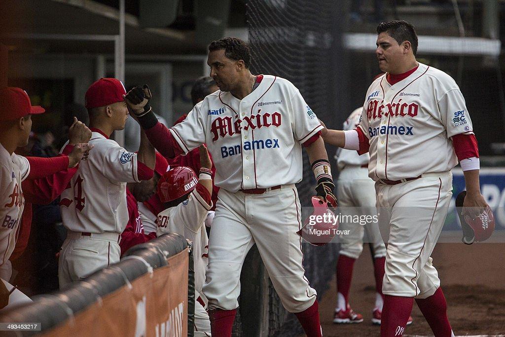 Luis Terrero and Japhet Amador of Diablos celebrate with teammates after scoring a run during a match between Diablos Rojos and Toros de Tijuana as...