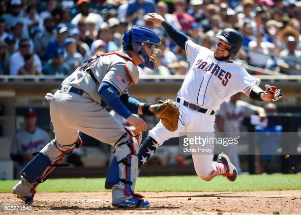 Luis Torrens of the San Diego Padres scores ahead of the throw to Yasmani Grandal of the Los Angeles Dodgers during the fiourth inning of a baseball...