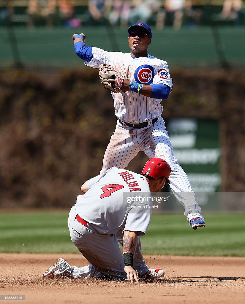 Luis Valbuena #24 of the Chicago Cubs leaps over Yadier Molina #4 of the St. Louis Cardinals to turn a double play in the 4th inning at Wrigley Field on May 8, 2013 in Chicago, Illinois.