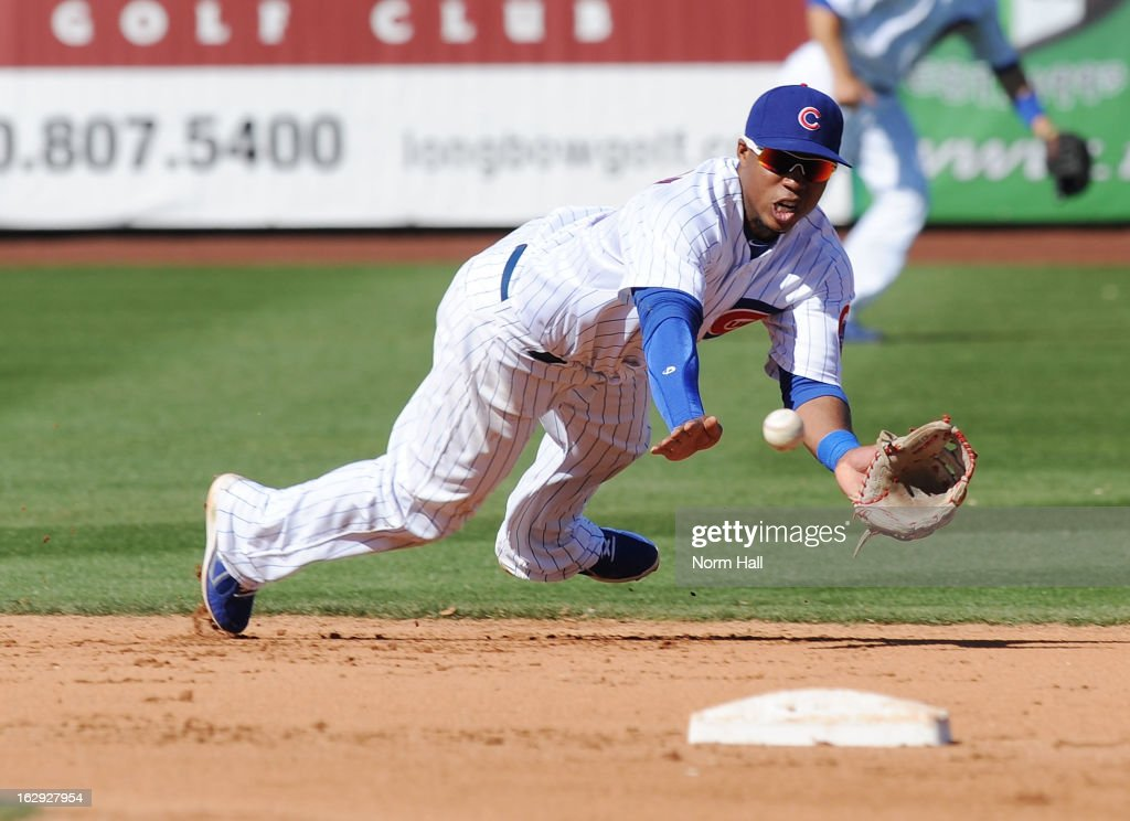 Luis Valbuena #24 of the Chicago Cubs makes a diving catch against the Arizona Diamondbacks at Hohokam Stadium on March 1, 2013 in Mesa, Arizona.