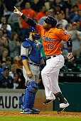 Luis Valbuena of the Houston Astros celebrates a solo home run in the seventh inning as Russell Martin of the Toronto Blue Jays looks on during their...