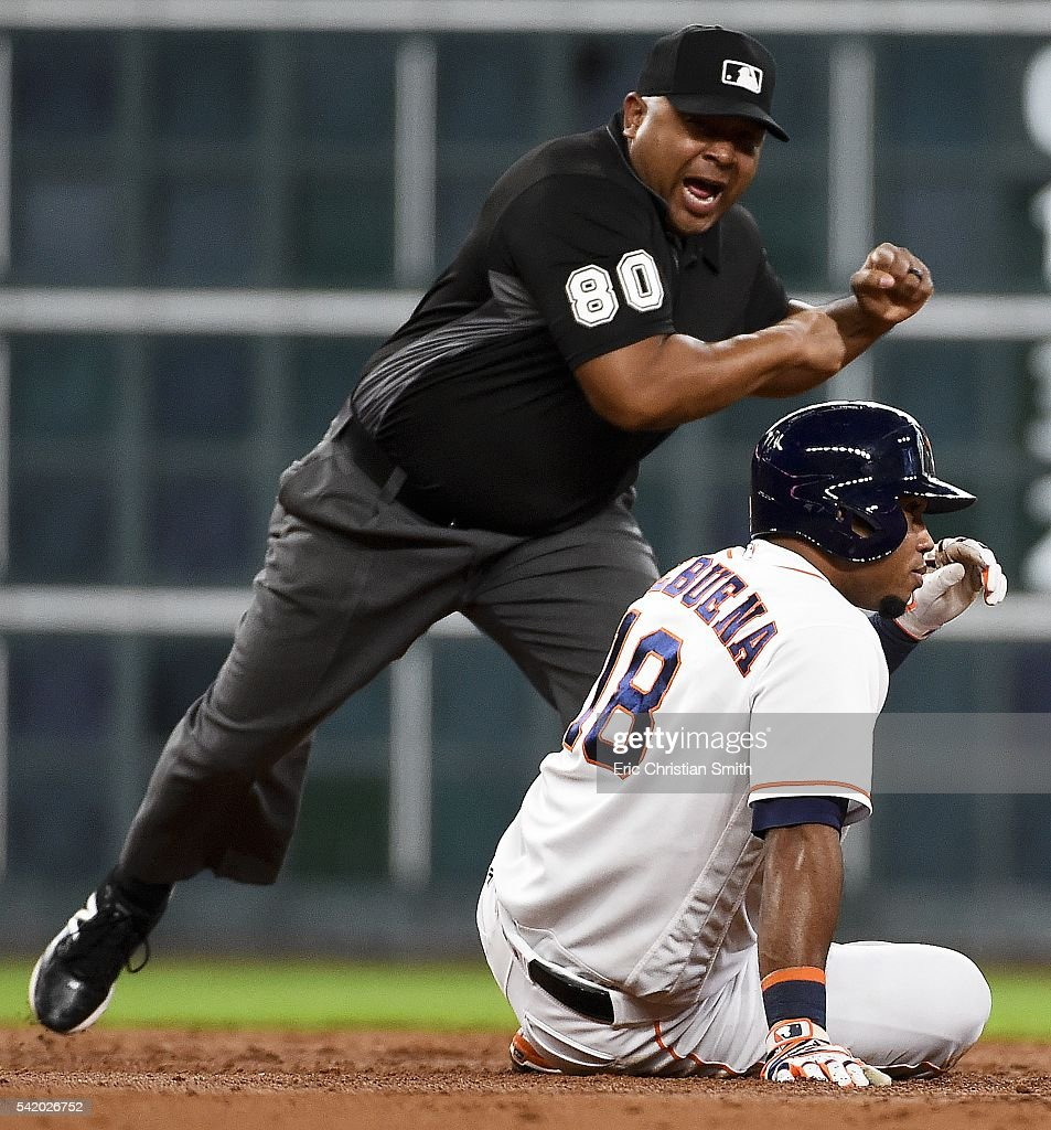 Luis Valbuena of the Houston Astros is called out by second base umpire Adrian Johnson after Valbuena was tagged out at second by Andrelton Simmons...