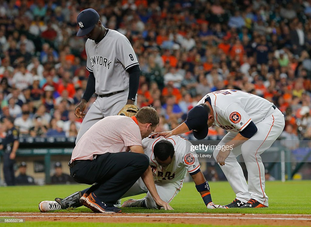 Luis Valbuena #18 of the Houston Astros is looked at by manager A.J. Hinch #14 of the Houston Astros, right, and head trainer Jeremiah Randall as Didi Gregorius #18 of the New York Yankees looks on after he stumbled running to first base in the second inning at Minute Maid Park on July 26, 2016 in Houston, Texas.