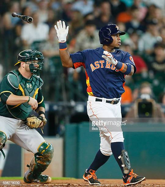 Luis Valbuena of the Houston Astros singles in the second inning as Stephen Vogt of the Oakland Athletics looks on at Minute Maid Park on June 5 2016...
