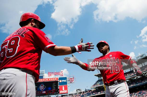 Luis Valbuena of the Los Angeles Angels of Anaheim celebrates with teammate Juan Graterol after hitting a solo home run in the fifth inning during a...