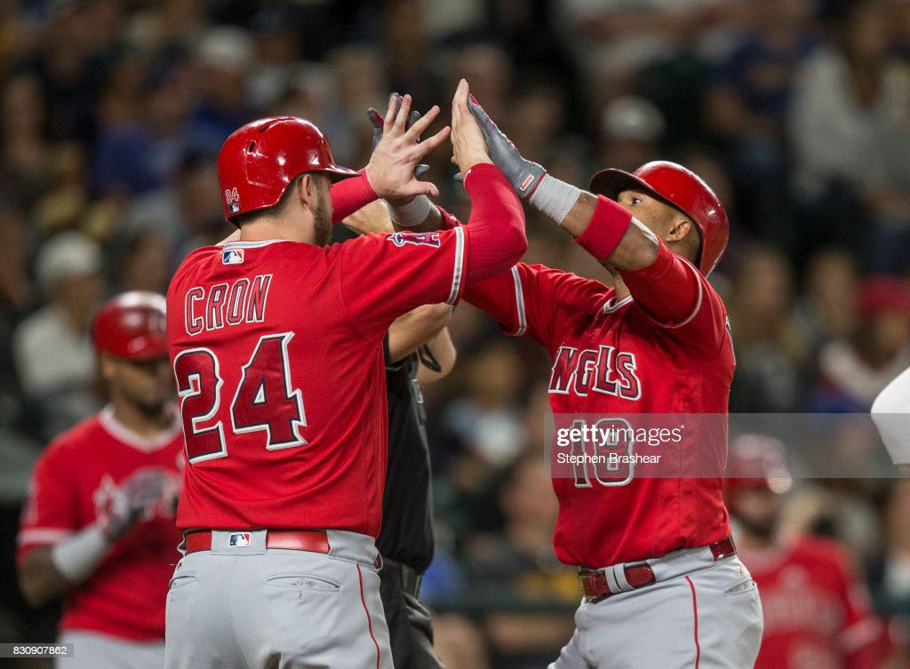 Luis Valbuena #18 of the Los Angeles Angels of Anaheim is greeted by C.J. Cron #24 of the Los Angeles Angels of Anaheim after hitting two-run home run off of relief pitcher Casey Lawrence #61 of the Seattle Mariners that also scored Cron during the seventh inning of a game at Safeco Field on August 12, 2017 in Seattle, Washington.