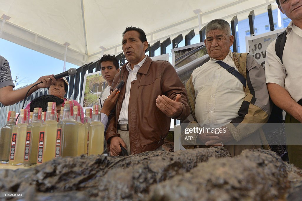 Luis Yanza (C), president of an organization of indigenous people affected by US oil company Chevron speaks as they prepare to hand on samples of earth and water contaminated with oil during a rally in front of the National Court of Justice in Quito, on July 26, 2012. The plaintiffs against Chevron will undertake more legal actions against Chevron overseas to be compensated wuith around USD 19,022 million for enviromental damage, one of the defendants' lawyers said Thursday. AFP PHOTO/RODRIGO BUENDIA
