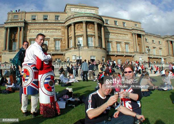 Luis Zambrand from Sydney and Lucy Homer from Dudley West Midlands toast with a glass of champagne in the gardens of Buckingham Palace as they wait...