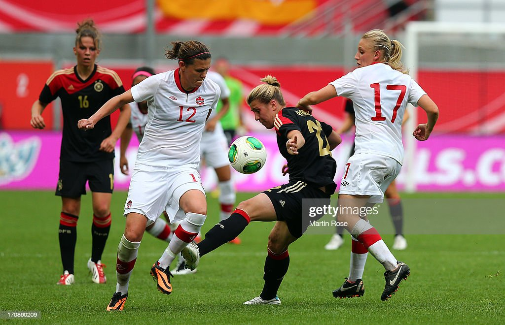 Luisa Wensing (C) of Germany and Christine Sinclair (L) and Melissa Bisque (R) of Canada battle for the ball during the Women's International Friendly match between Germany and Canada at Benteler Arena on June 19, 2013 in Paderborn, Germany.
