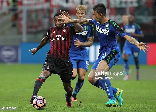 Luiz Adriano of AC Milan is challenged by Francesco Acerbi of US Sassuolo during the Serie A match between AC Milan and US Sassuolo at Stadio...