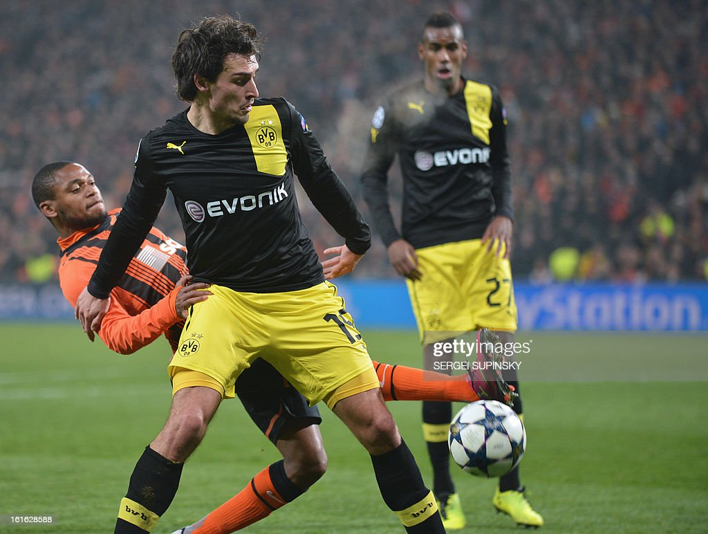 Luiz Adriano (L ) of FC Shakhtar fights for a ball with Mats Hummels (R) of Borussia Dortmund during their UEFA Champions League round 16 football match in Donetsk on February 13, 2013. AFP PHOTO/ SERGEI SUPINSKY