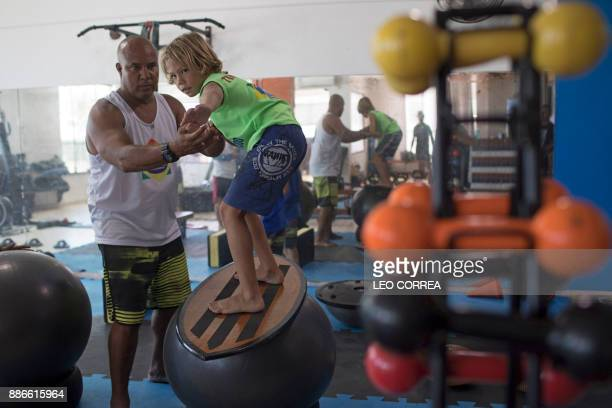 Luiz Augusto de Matos one of the teachers at 'Saquarema Surf School' assists his pupil Miguel Cortinhas at the 'Inside Fit' training centre during a...