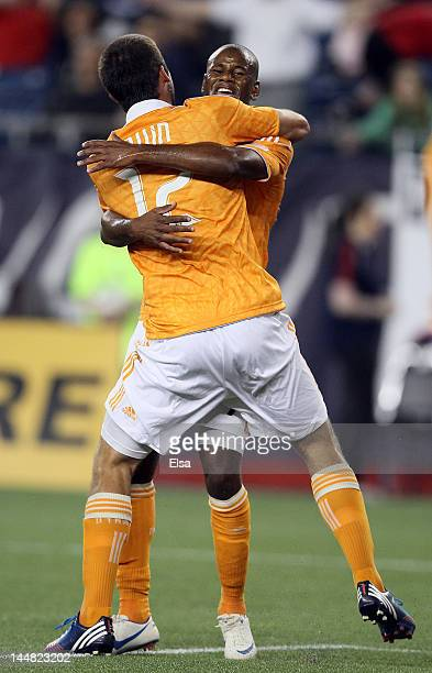 Luiz Camargo of the Houston Dynamo is congratulated by teammate Will Bruin after Camargo scored a goal to tie the game with the New England...